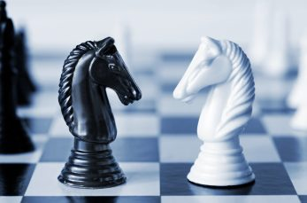 Head to head - knights on a chess board, in blue duotone.  Shallow depth of field.